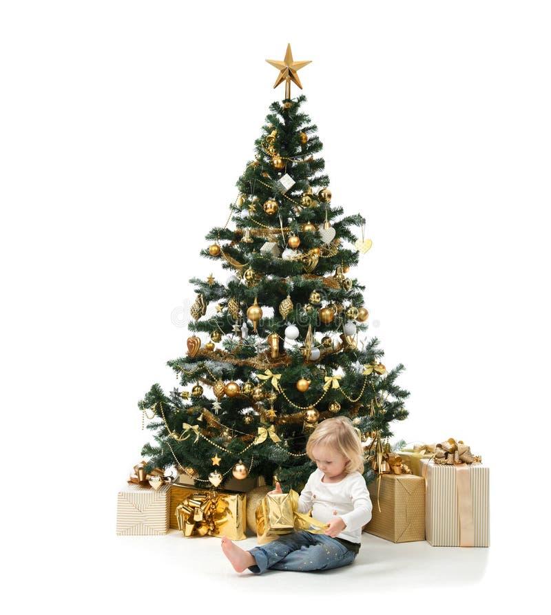 La sentada del niño del bebé del niño y abre el presente del Año Nuevo cerca de la decoración fotografía de archivo