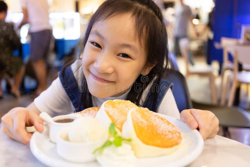 La sentada feliz atractiva de la muchacha y come el postre, cierre encima del retrato fotos de archivo libres de regalías
