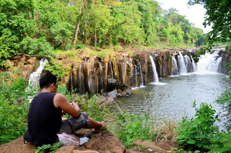 La sentada gorda tailandesa del hombre y se relaja en piedra en la cascada de Tad Pha Suam imagenes de archivo