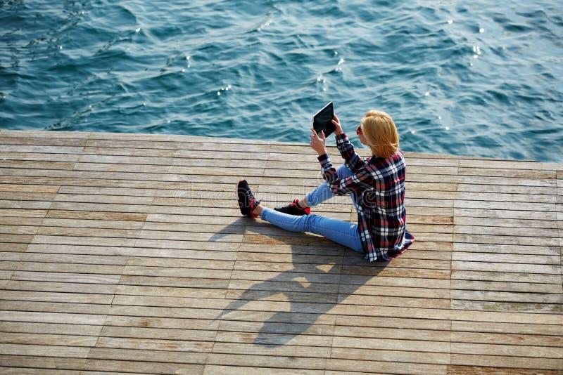 La sentada joven dulce en el embarcadero que disfruta del tiempo hermoso y envía la imagen al individuo fotos de archivo