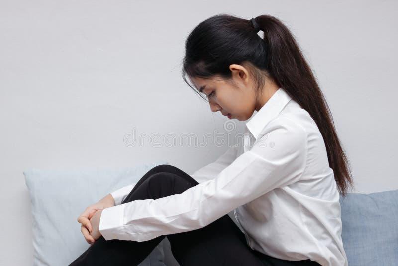 La sentada y la curva asiáticas jovenes subrayadas ansiosas de la mujer abajo dirigen en sala de estar foto de archivo