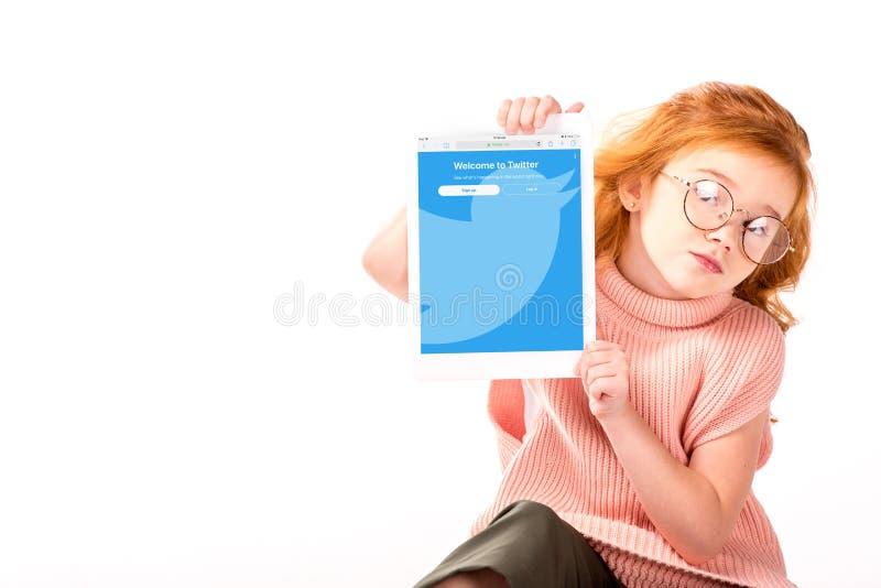 la sentada y la demostración rojas del niño del pelo cargaron la página del gorjeo en la tableta imagen de archivo libre de regalías