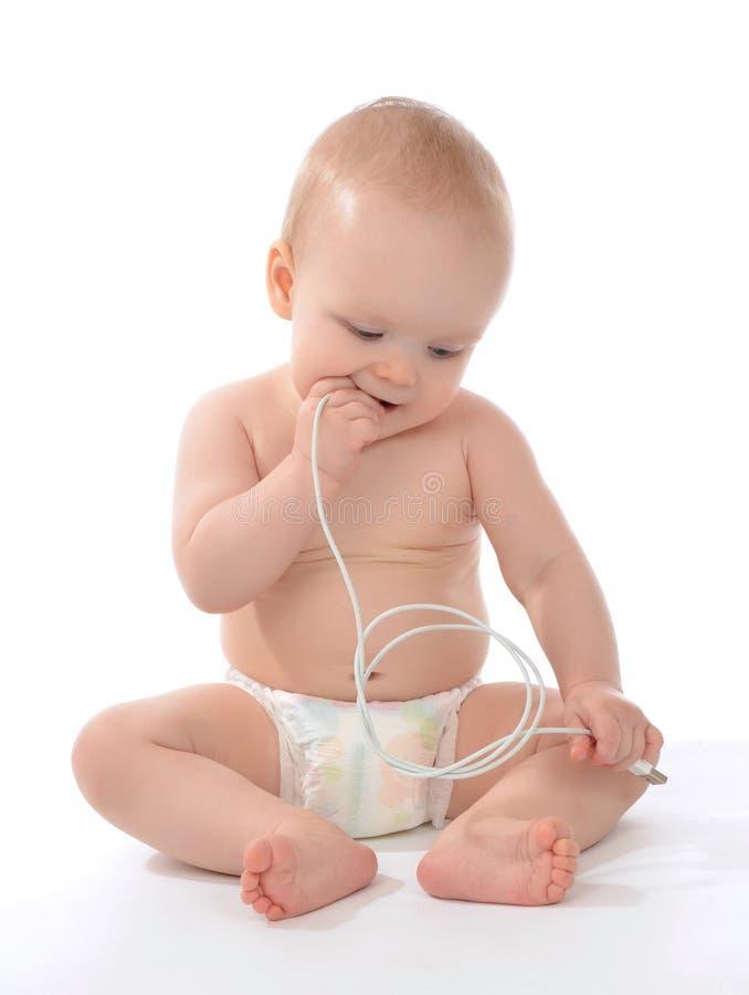 La sentada y el control infantiles del bebé del niño en manos accionan el cargador c imagen de archivo libre de regalías
