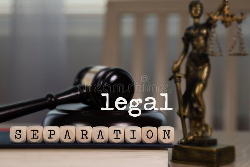 La SEPARACIÓN LEGAL de las palabras integrada por de madera corta en cuadritos Mazo y estatua de madera de Themis en el fondo fotos de archivo