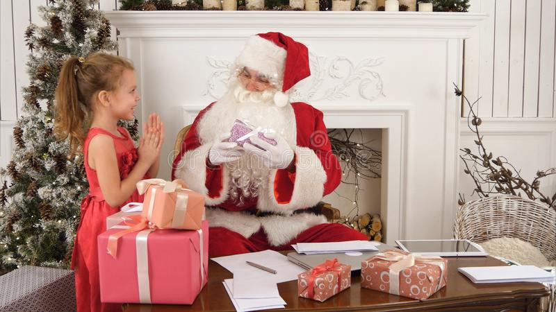La separazione occupata di Santa chidlren le lettere del ` s mentre piccolo assistente sveglio gli che porta un regalo fotografia stock libera da diritti