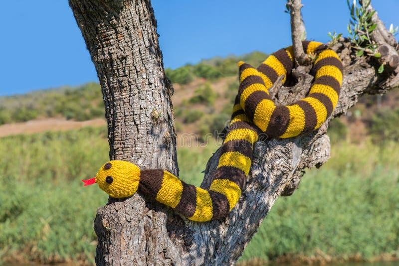 La serpiente hecha punto falsificación cuelga en tronco de árbol fotografía de archivo