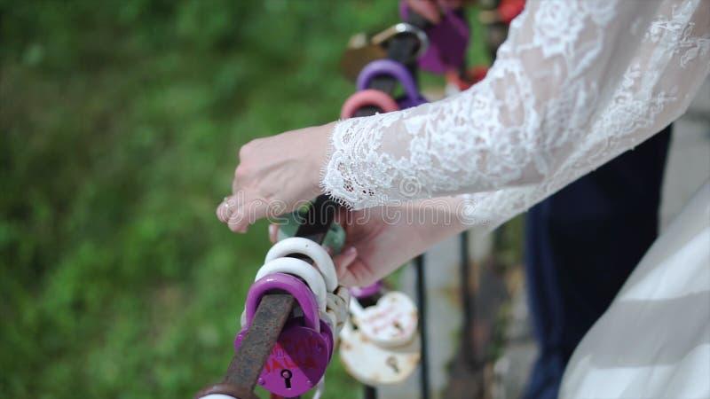 La serratura decorativa in mani delle persone appena sposate clip Simbolo di nozze di amore eterno, serratura in mani della sposa immagine stock libera da diritti