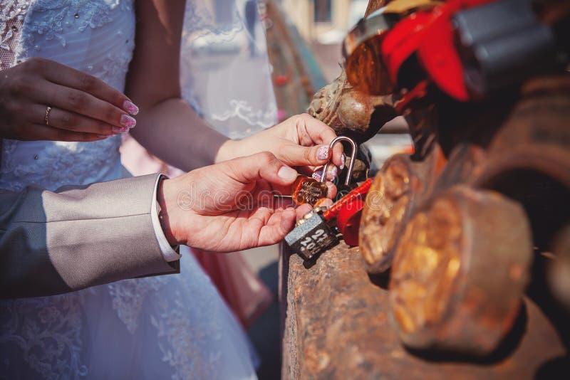 La serratura in mani delle persone appena sposate fotografie stock