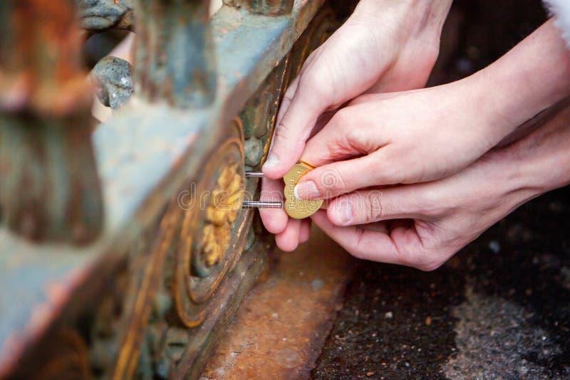La serratura in mani delle persone appena sposate immagine stock