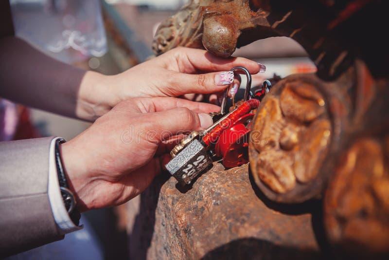 La serratura in mani delle persone appena sposate fotografia stock