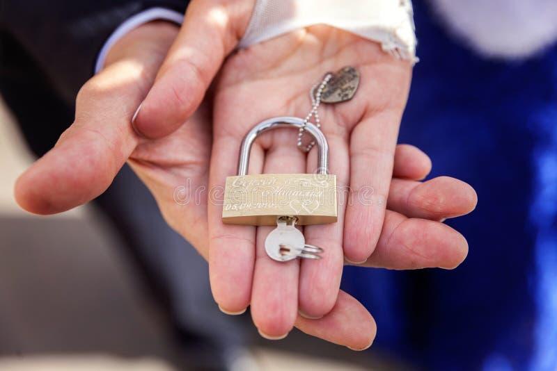 La serratura in mani delle persone appena sposate immagini stock libere da diritti