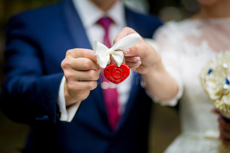 La serratura in mani recentemente della coppia sposata, primo piano immagine stock libera da diritti