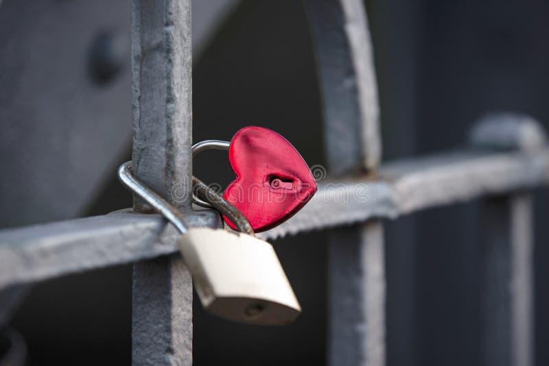 La serrure en métal sous forme de coeur rouge accroche sur le structu en métal image libre de droits