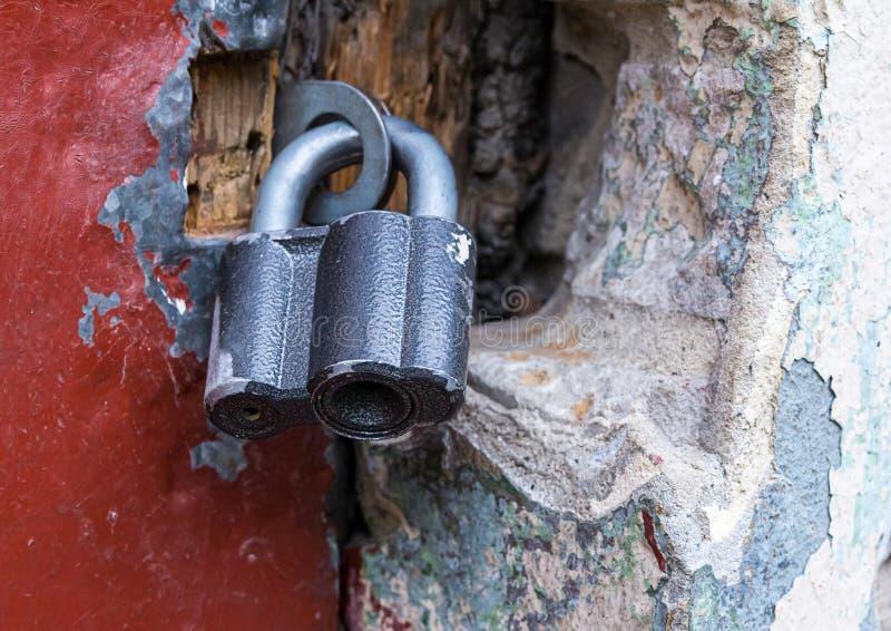 La serrure fermée a articulé accrocher noir en métal sur des charnières sur un fond en pierre et un en bois rouge image libre de droits