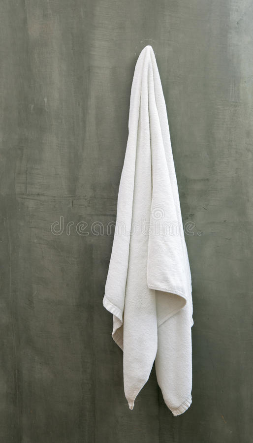 La serviette blanche accrochante a drapé sur le mur en béton d'Exposive image stock