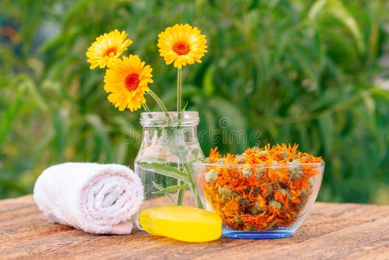 La serviette, savon avec l'extrait de souci, calendula fleurit dans un verre images stock