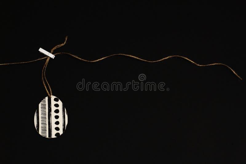 La servilleta estilizada adornó el huevo para el decoupage en blanco y negro en el cordón del yute con la pinza en fondo negro Es fotografía de archivo
