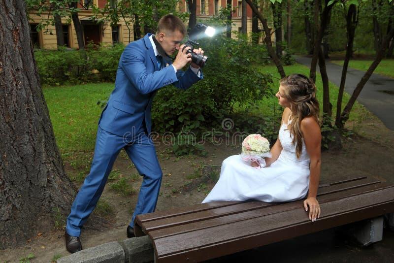La sesión fotográfica de la boda, recién casado con una cámara, toma bri de las imágenes imagen de archivo libre de regalías