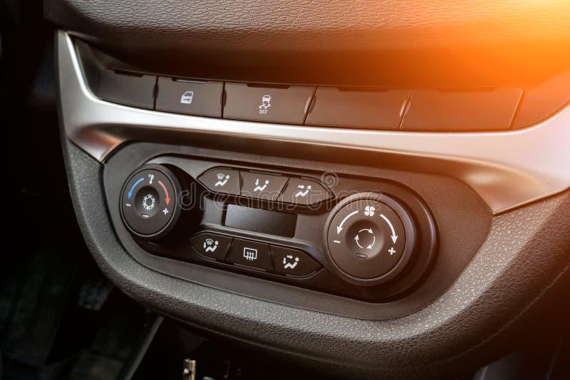 La sezione comandi centrale sul pannello dentro il primo piano dell'automobile con controllo di clima e l'audio sistema e un foro fotografia stock libera da diritti