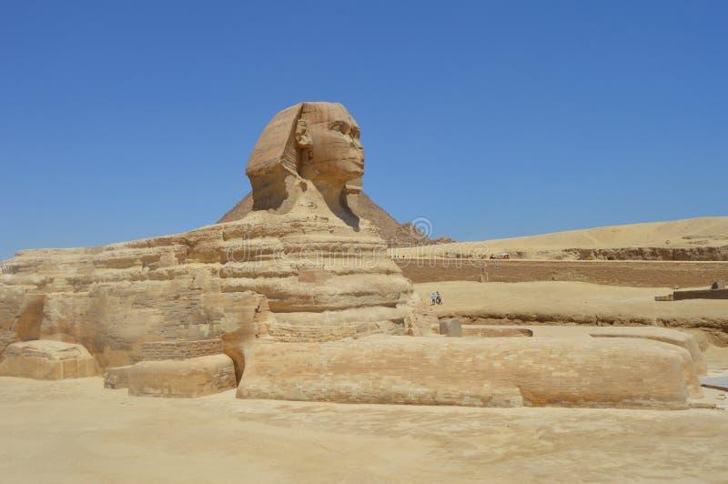 La Sfinge sta fiera davanti alla grande piramide, Il Cairo, Egitto fotografie stock libere da diritti
