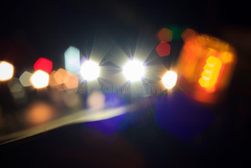 La sfuocatura di Bokeh dell'automobile si accende sulla via alla notte fotografie stock libere da diritti