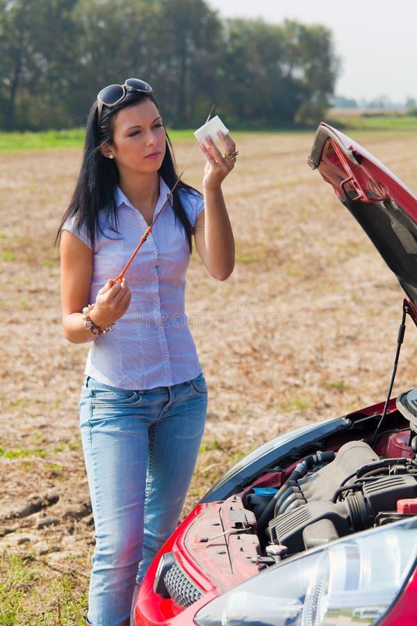 La sig.ra misura la pressione di olio in sua automobile fotografie stock libere da diritti