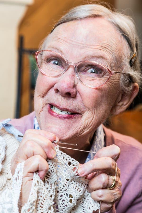 La signora anziana pazza con lavora all'uncinetto fotografia stock