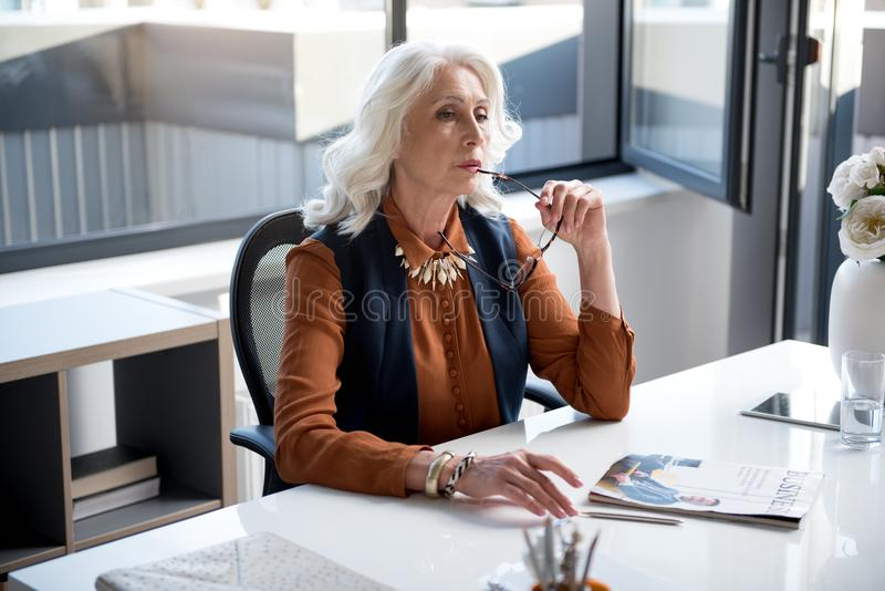 La signora anziana seria sta lavorando in ufficio fotografie stock libere da diritti