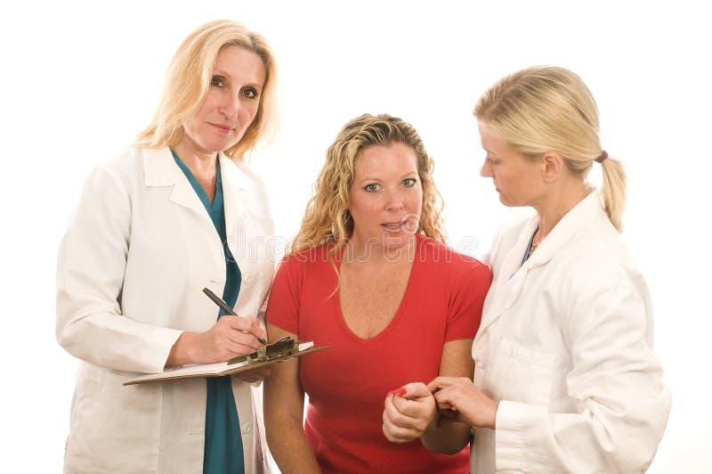 La signora falsifica i vestiti medici con il paziente fotografia stock