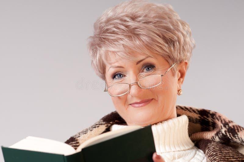 La signora maggiore con un libro fotografie stock