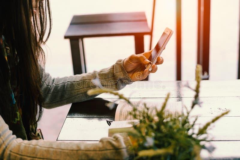La signora si siede e si rilassa nel caffè, giudicante il telefono disponibile immagine stock