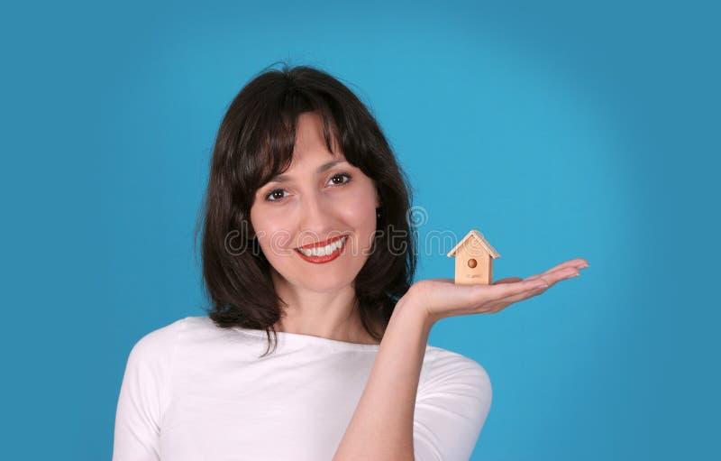 La signora sta tenendo la casa di legno immagine stock