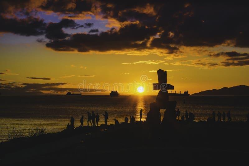 La silhouette d'Inukshuk avec le coucher du soleil opacifie des milieux de ciel photo libre de droits