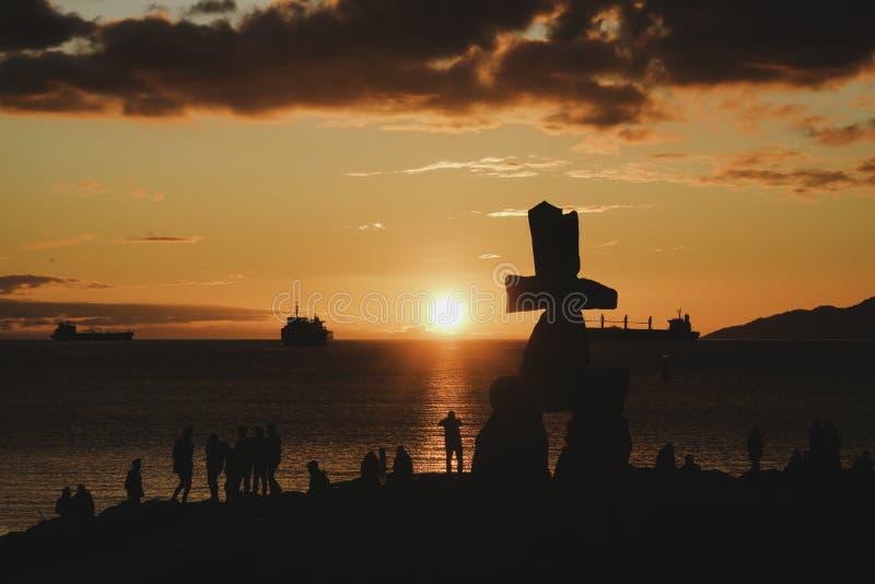 La silhouette d'Inukshuk avec le coucher du soleil opacifie des milieux de ciel photos stock