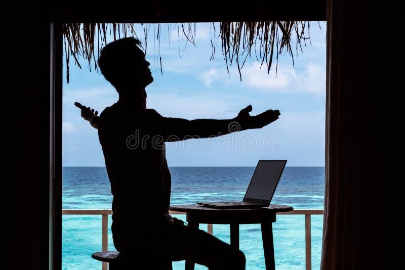 La silhouette d'un jeune homme avec des bras a soulevé le fonctionnement avec un ordinateur sur une table L'eau tropicale bleue c images stock