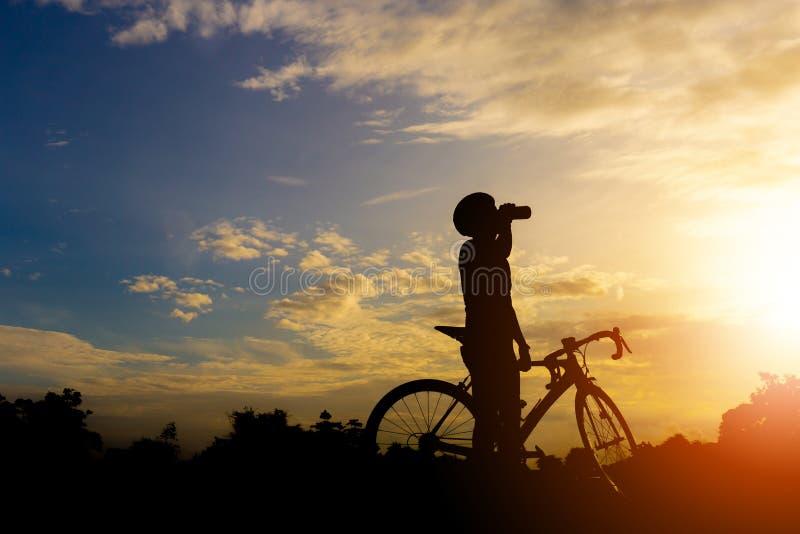 La silhouette d'un mâle de cycliste détendent et eau potable avec la route photo libre de droits