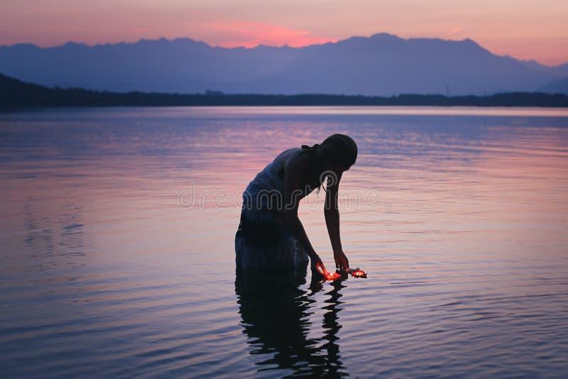 La silhouette d'une femme dans le lac pourpre arrose image stock
