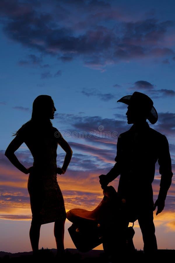 La silhouette d'une femme dans les hanches serrées de mains de robe semblent le cowboy latéral photographie stock libre de droits