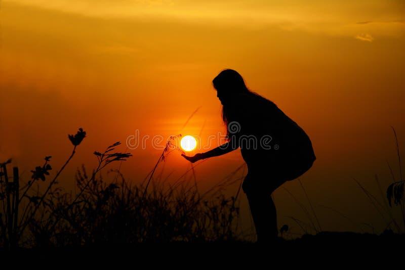 La silhouette d'une femme tient le soleil a un fond de coucher du soleil photos libres de droits