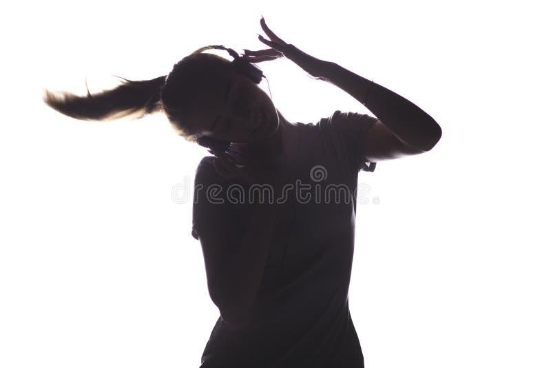 La silhouette d'une fille écoutant la musique dans des écouteurs, jeune femme détendant sur un blanc a isolé le fond, le concept  photo stock