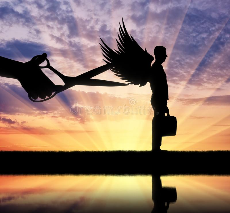 La silhouette d'une grande main avec des ciseaux prévoit pour tailler les ailes d'un homme image libre de droits