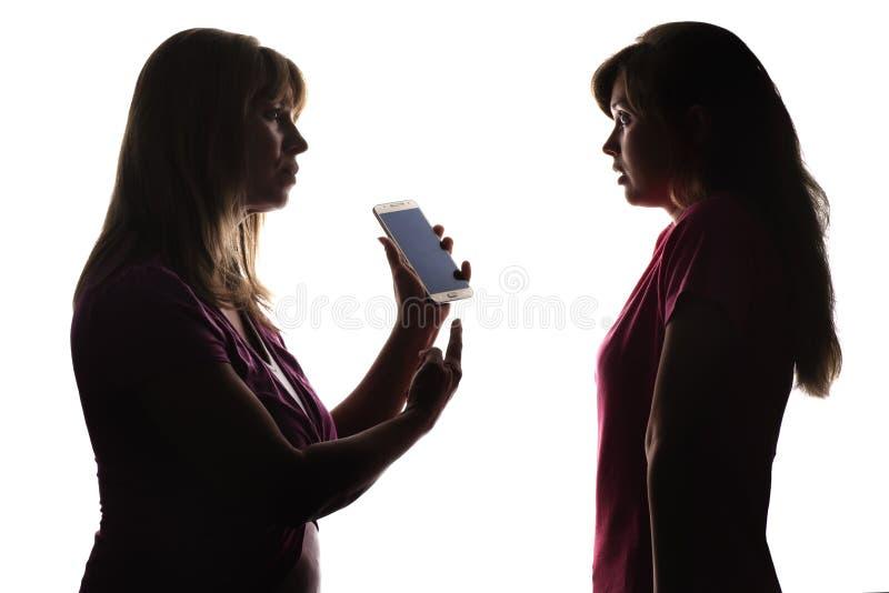 La silhouette d'une mère indignée avec un téléphone du ` s de fille, un adolescent a peur photos libres de droits