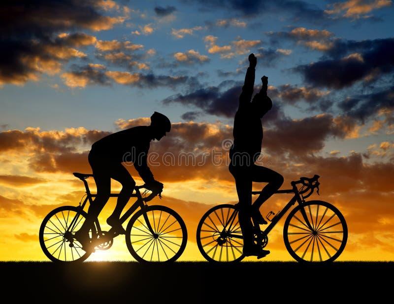 La silhouette de deux cyclistes montant une route font du vélo images stock