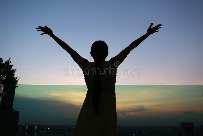 La silhouette de la femme étirant des bras apprécient détendent au coucher du soleil sur le dessus de toit du bâtiment photo stock