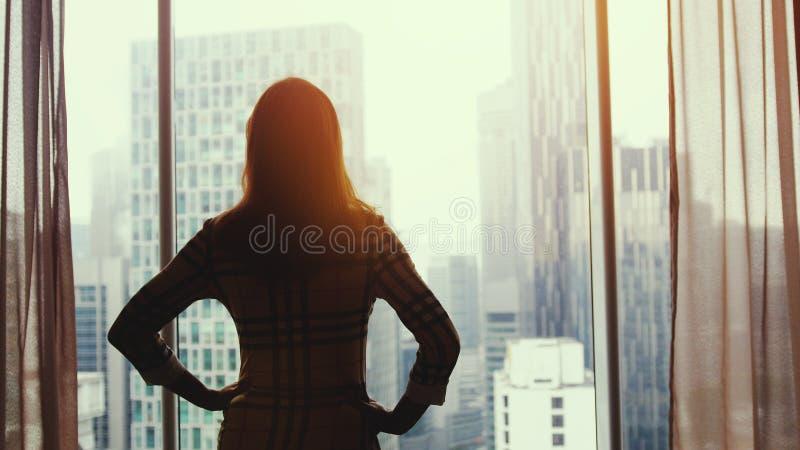 La silhouette de la jeune femme réussie admire la vue de ville de la fenêtre dans le bureau pendant le coucher du soleil stupéfia photos stock
