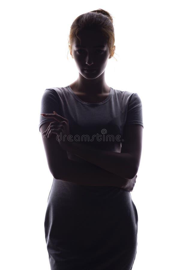 La silhouette de la jeune femme sûre regardant tout droit un blanc a isolé le fond images libres de droits