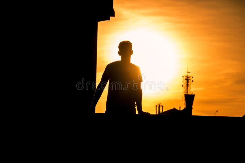 La silhouette de l'homme dans un coucher du soleil photo stock