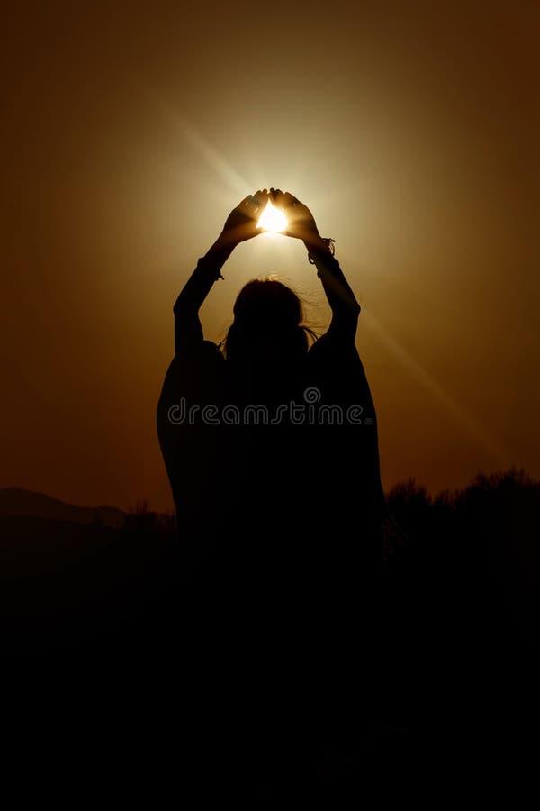 La silhouette de la femme remet tenir le soleil dans la triangle sur le fond photos libres de droits