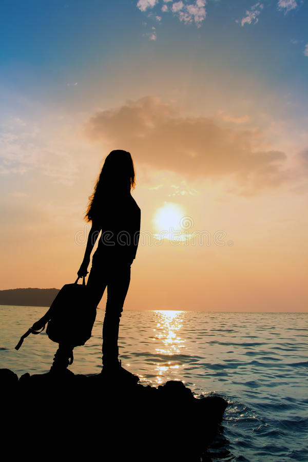 La silhouette de la fille avec le sac à dos au coucher du soleil photos libres de droits