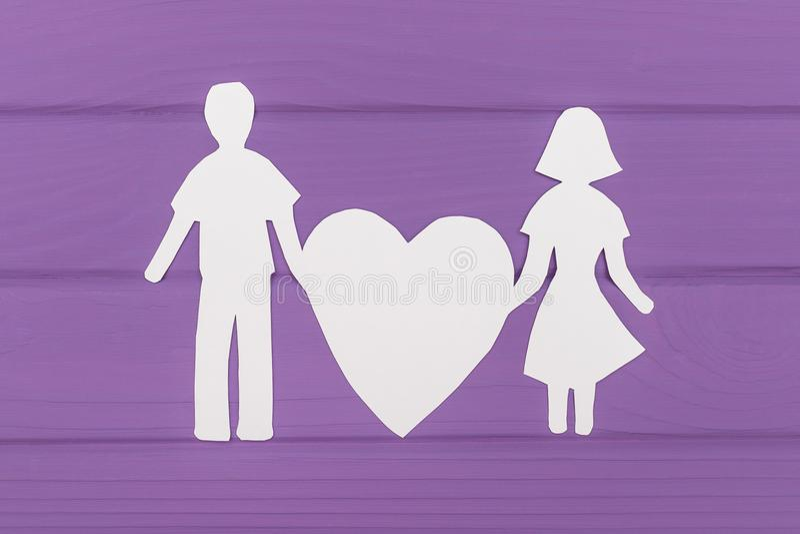 La silhouette de papier de l'homme et de la femme tient le grand coeur photo libre de droits